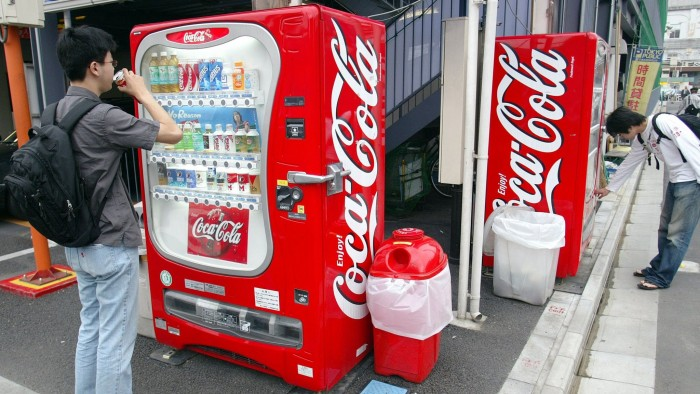 Tokyo residents purchase soft drinks from a Coca-Cola vending machine in Tokyo Thursday, June 26, 2003. The world's largest soft-drink maker inflated its fountain revenue in Japan, said a fired executive whose earlier lawsuit led the company to disclose that employees rigged a marketing test. Photographer: Tatsuyuki Tayama/Bloomberg News