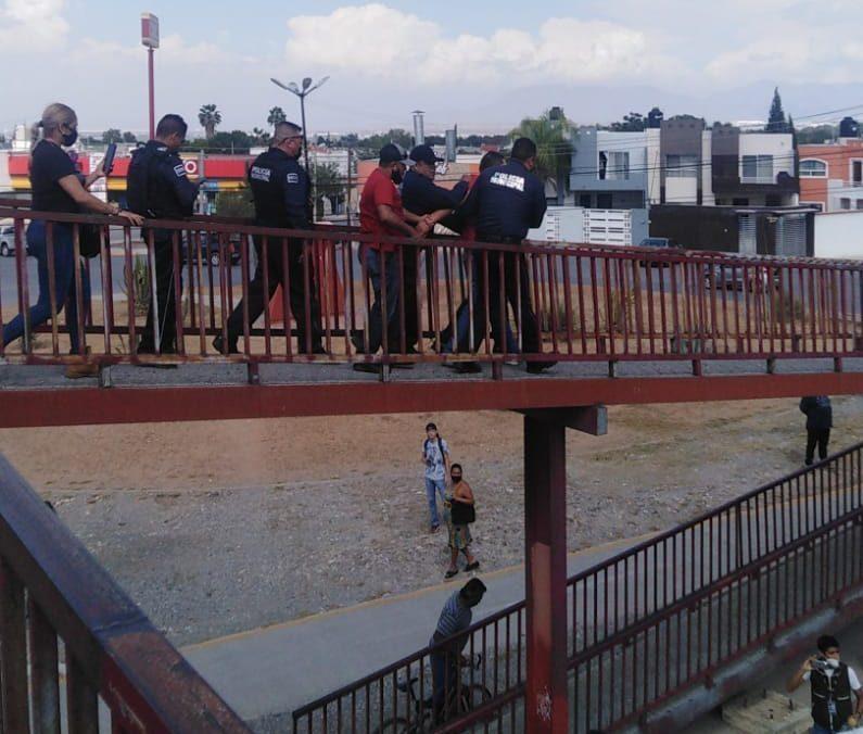 Policía y bombero rescatan a persona que intentó lanzarse de puente peatonal